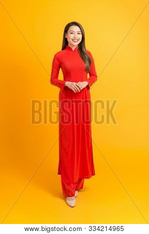 Happy Lunar New Year. Asian Girl In Vietnamese Traditional Dress (ao Dai) On Yellow Background