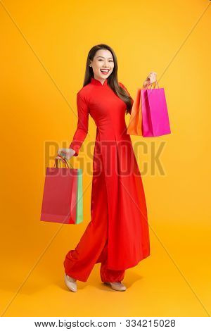 Asian Lady In Red Ao Dai Dress Holding Shopping Bags Isolated On Yellow Background, Happy Lunar New