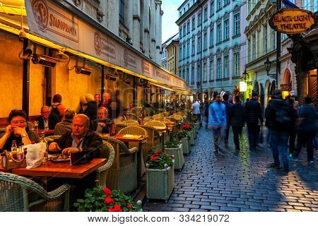 PRAGUE, CZECH REPUBLIC - SEPTEMBER 22, 2015: People sitting in illuminated outdoor restaurant next to crowd cobblestone street in Old Town of Prague - famous and popular travel destination.