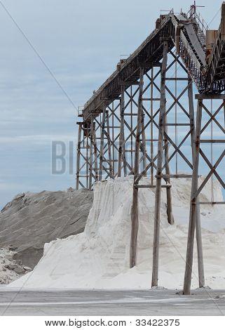 Pile of sea salt under conveyor of saline refinery