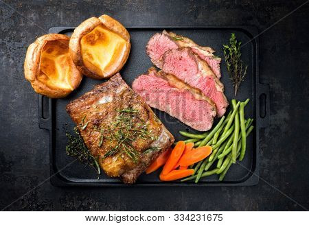 Traditional Commonwealth Sunday roast with sliced cold cuts roast beef with vegetable and Yorkshire pudding as top view on a modern design cast iron tray