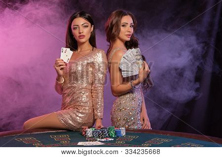 Two Women Showing Cards And Money, Posing At Playing Table In Casino. Black, Smoke Background With C