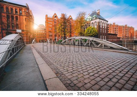 Arch Bridge Over Canals With Cobbled Road In The Speicherstadt Of Hamburg, Germany, Europe. Historic
