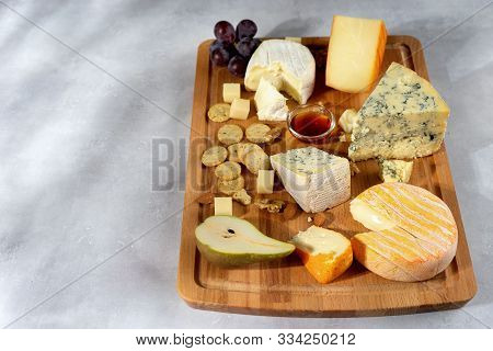Many Sorts Of Cheeses Served On Wooden Board