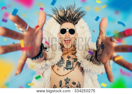 A portrait of a cool young punk man posing in the studio. Casual punk fashion, beauty.