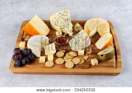 Many Sorts Of Cheese Peaces Served On Wooden Board