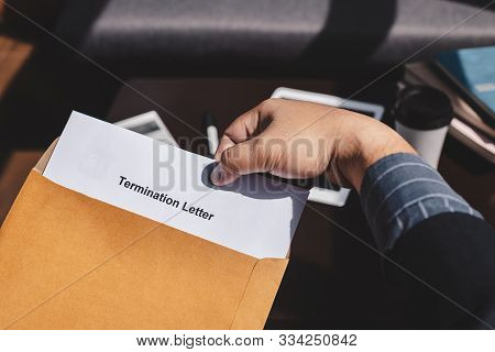Termination Of Employment And Layoff Concept, Businessman Holding Termination Of Employment Form