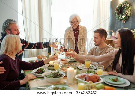 Young and senior members of big family clinking with glasses of wine over served festive table during Thanksgiving dinner