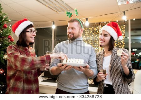 Happy young businessman offering dessert to his pretty colleagues with champagne at Christmas party in office