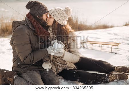Happy Couple In Love Sitting On Snow Having Fun In Warm Casual Winter Clothes On A Sunny Day In Wint