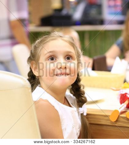 Happy Little Girl Sitting In A Childrens Caf .