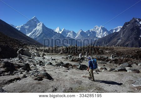 Everest trek, Man hiking in Himalayas with view of Ama Dablam mountain. Sagarmatha national park, Solukhumbu, Nepal