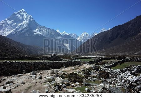 Old stone walls near Pheriche, Everest trek, View of Ama Dablam (6856 m) in Himalayas mountains, Sagarmatha national park, Solukhumbu, Nepal