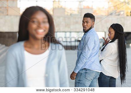Infidelity Concept. Unfaithful Black Womanizer Guy Turning Around Amazed At Another Woman While Walk