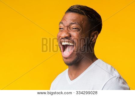 Laughter. Portrait Of Afro Guy Laughing Out Loud Standing On Yellow Background In Studio. Copy Space