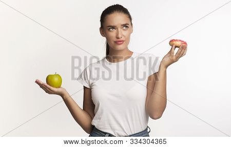 Puzzled Girl Choosing Between Donut And Apple Standing Over White Studio Background. Healthy Vs Unhe
