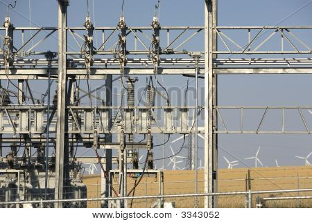 Power Transformer Yard Wth Wind Turbines In The Background