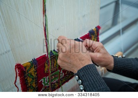 Weaving And Manufacturing Of Handmade Carpets Closeup. Womens Hands Weave A Carpet . Woman Hands Wea