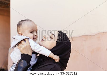 Young Muslim Woman In Hijab Holding Her 1-year-old Baby Boy, Hugging And Kissing. Happy Muslim Mothe