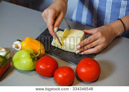 Young Woman Cuts The Cheese Next To A Vegetable Table.