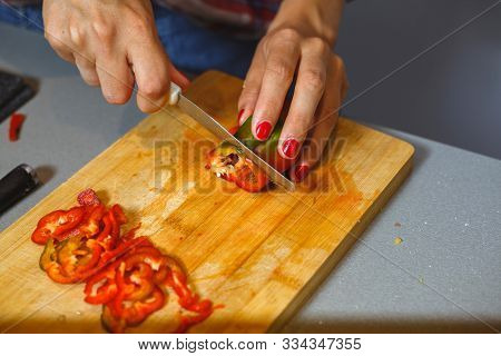 Young Girl Slices Pepper On A Wooden Countertop.