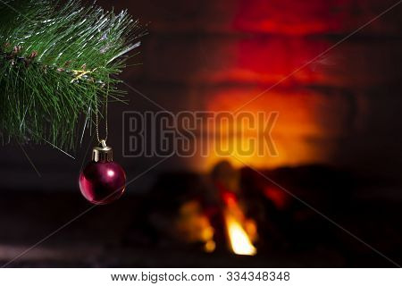 Red Ball On A Christmas Tree Near A Burning Fireplace, Close-up, Christmas Composition.
