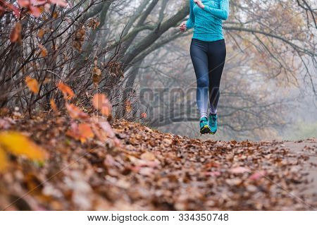 Woman Jogging Jumping In Forest, No Face. Fallen Foliage On The Ground, Autumn Foggy Morning. Shooti
