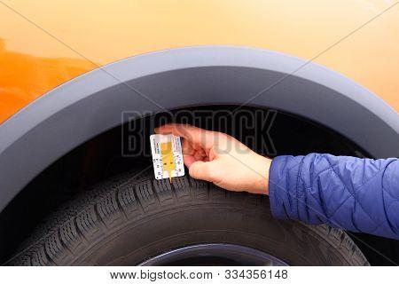 Measuring Profile In Hand. Tread Depth Meter At Tire In Orange Car. Man Is Measuring The Tread Depth