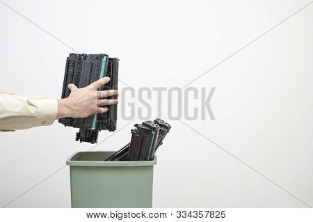 Male Hands Of An Office Worker Stack Spent Cartridges In A Bucket Against A White Wall.