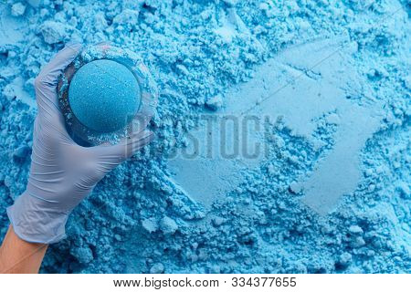 Blue Bath Bomb In Hand On Dry Mixture Background, Copy Space. Cosmetics Manufacture Process.
