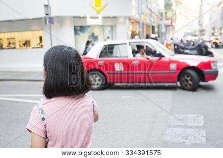 Young Woman Walking In Hongkong Street With Taxi Cab In Background. Traveler Asian Girl In Hongkong