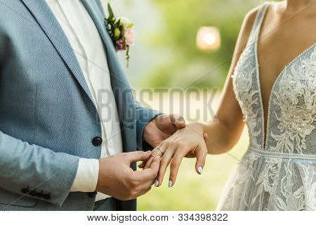 Man Wearing Wedding Ring On Woman Hand Close Up. Symbol Of Love And Commitment. Wedding Ceremony Vow