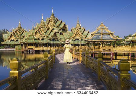 A Woman Tourist Is Sightseeing Beautiful Golden Pavilion Inside Ancient City (muang Boran) In Thaila