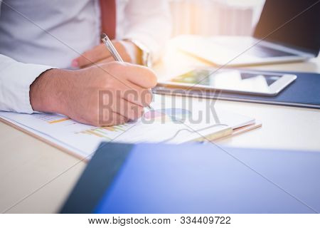 Businessman, Office Guy Working On Paperwork At Office. Handsome Young Man Writing, Analyzing Graph,