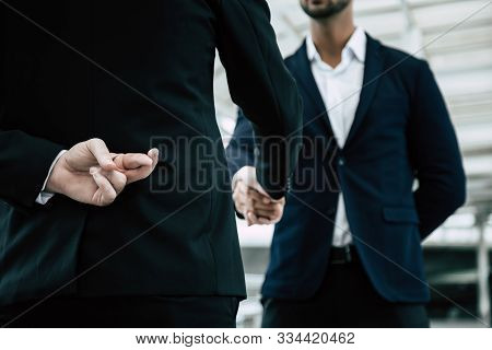 Businessman Or Politician Cross Finger, Hiding Behind His Back During He Get Handshake To Another Pe