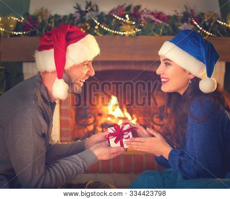 Christmas Gift in hands. Happy Man giving Christmas and New Year Gift box to woman at Home. Family Xmas celebration. Happy smiling Couple Holding, Receiving Gift box. Christmas decoration Relationship
