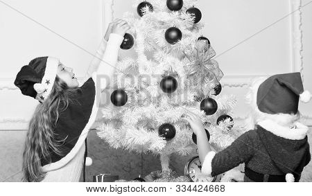 Boy and girl decorating tree. Cherished holiday activity. Kids in santa hats decorating christmas tree. Family tradition concept. Children decorating christmas tree together. Siblings busy decorating poster