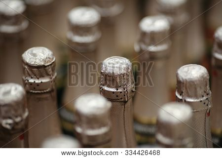 Focus On Celebratory Sparkling Wine Tops With Silver Foil In Wine Store. Associated With Celebration