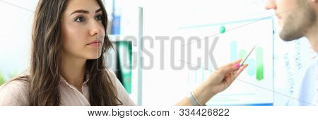 Portrait Of Smart Businesswoman Pointing At Presentation Board And Looking At Colleague With Interes