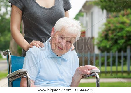 Happy Senior Lady In Wheelchair With Caregiver