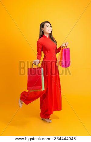 Beautiful Asian Girl Holding Colorful Shopping Bags While Wearing Ao Dai Vietnam Over Yellow Backgro