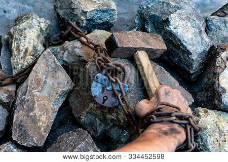 The Dirty Hands Of A Slave Hold A Hammer Among The Stones. Slave Hard Labor In The Quarries. The Sym