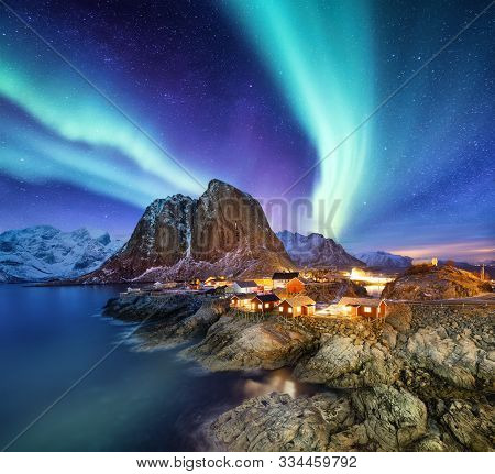 Aurora Borealis Above Reine, Lofoten Islands, Norway. Nothen Light, Mountains And Houses. Winter Lan