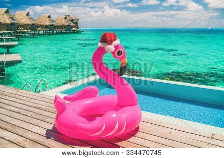 Christmas summer vacation pool float pink flamingo wearing santa hat travel background winter holidays. Traveling south to enjoy sun and heat at luxury resort overwater bunglaows in Bora Bora, Tahiti.