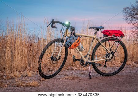 touring bicycle at dusk with headlight on in late fall or winter scenery in northern Colorado - a gravel trail in RIvebrnd Ponds Natural Are in Fort Collins