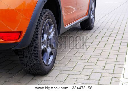 Orange Car Is Parked In Its Parking Spot In City. Close Up Car Wheel, Urban Environment.