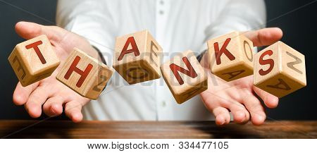 Blocks thrown by a man with letters form the word Thanks. The person brings his thanks and appreciates the service or help rendered to him. A polite answer, mutual assistance and support. poster