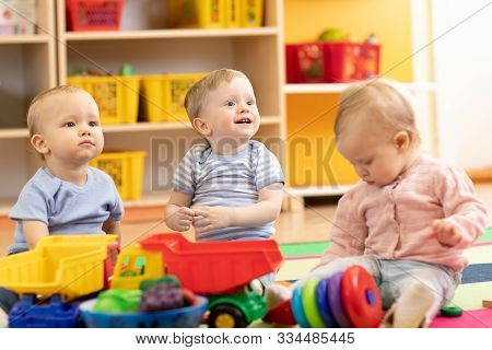 Little Toddlers Boys And A Girl Playing Together In Kindergarten Or Creche. Preschool Children In Da