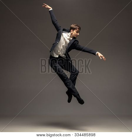Man In Casual Office Style Clothes Jumping And Dancing Isolated On Grey Background. Art, Motion, Act