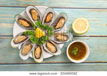 Mussels With Herbs With Lemon Parsley In The Table / Steamed Mussels Served On White Plate And Sauce